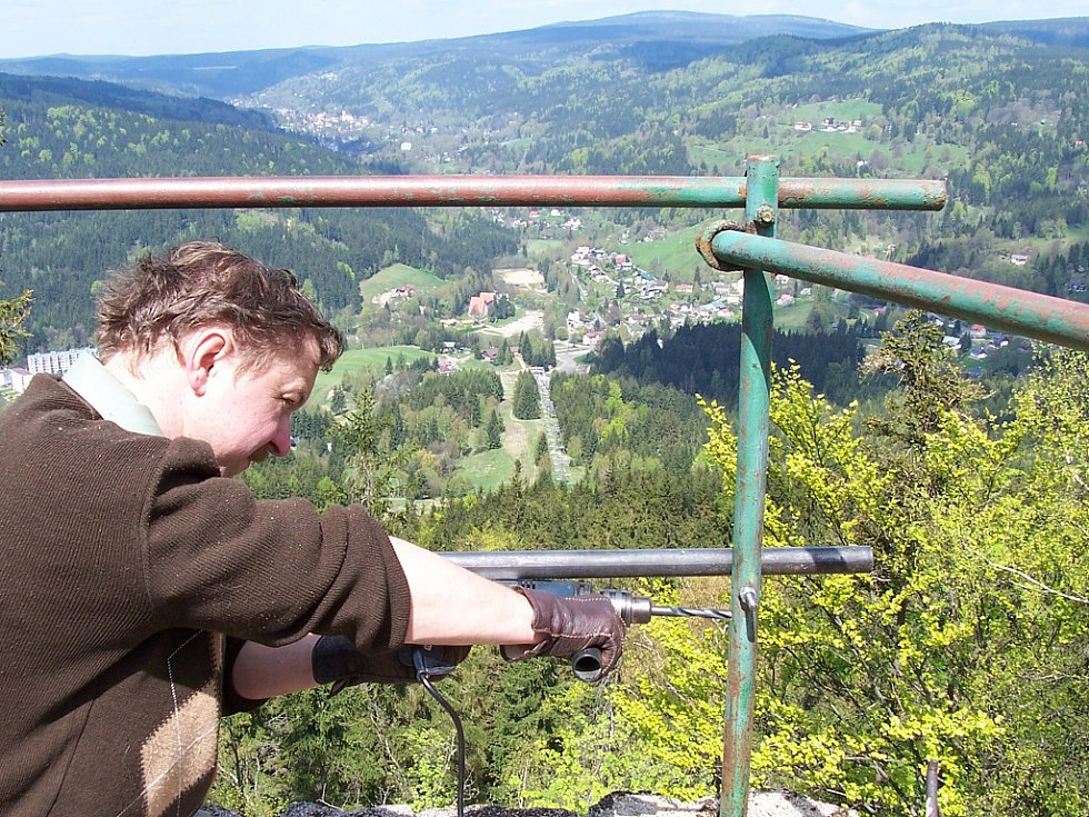 Oprava vyhlídky na Tanvaldském Špičáku. Jiří Frigo Novák z Jizersko-horského spolku připravil kolegům zábradlí k připevnění chybějících částí.
