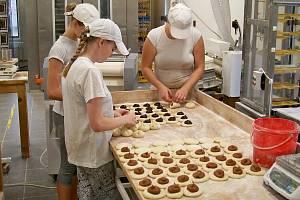 V řemeslné pekárně Lukáše Maška ve Velkých Hamrech se vše dělá ručně. Zaměstnankyně právě balí buchty.