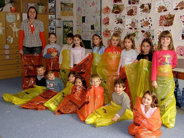 Žáci první třídy Základní školy Pelechovská kvůli fotografování do nového ekologicky zaměřeného kalendáře neváhaly vlézt do pytlů na třídění plastů a nápojových kartonů.