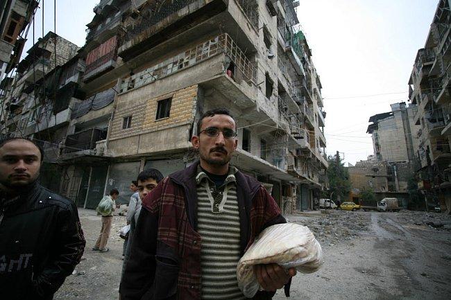 Obyvatel Aleppa uprostřed zničené čtvrti Al Shaar.
