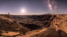 Silueta fotografa v utažském Moabu se rýsuje proti noční obloze, která odhaluje galaxii Andromedu, Mléčnou dráhu a Měsíc. snímek vyhrál velkou cenu v každoroční astronomické fotografické soutěži pořádané Královským muzeem v Greenwichi.