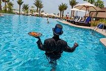 """Brigádník, který nedávno dorazil zGhany, v roli """"bazénového velvyslance"""" obsluhuje žíznivé plavce v pětihvězdičkovém dubajském hotelu Ritz-Carlton."""