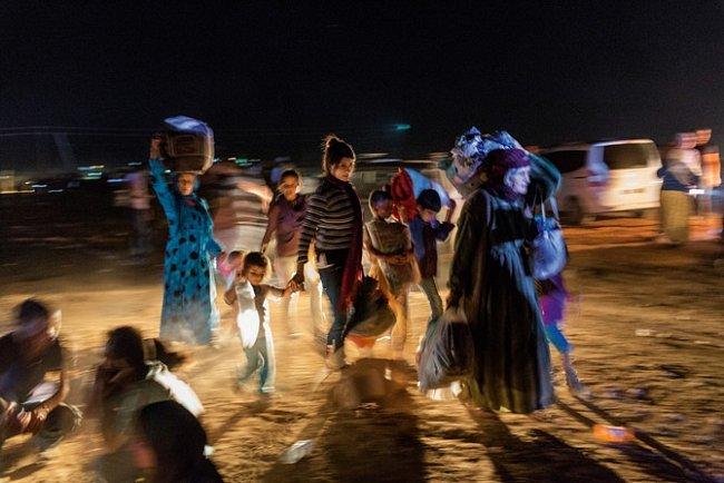 Celé hodiny poté, co turečtí vojáci vyříznou do hraničního plotu díru, uprchlíci zAjn al-Arab neustávají proudit přes hranice. Nesou si jen šaty, jež právě mají na sobě, a pár tašek, které si ve spěchu sbalili.