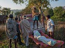 Muž stojící naplošině nákladního auta nakládá tělo svého syna vevesnici Hésó vestátu Džhárkhand. Nakulu Mundu, kterému ještě nebylo ani dvacet, zastřelili naksalité zato, že byl údajně policejním donašečem.