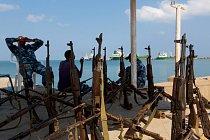 Příslušníci pobřežní hlídky vDžíbútí vyzbrojení starými kalašnikovy sledují vodní cestu Báb al-Mandab. Raní lidé opouštěli Afriku přes tuto úžinu. Salopek zde chytil loď doSaúdské Arábie, aby pokrač