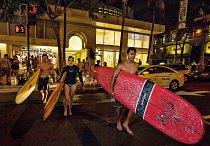 Surfaři přecházejí rušnou Kalakaua Avenue podni ježdění nadlouhých klidných vlnách, které se valí naWaikiki Beach. Pobřeží této oblasti lemují drahé obchody, luxusní byty agrandhotely. Průchody mezi budovami umožňují přístup naoblíbenou pláž svlnami