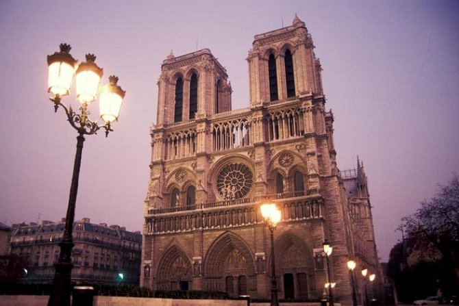 Notre Dame osvětlují za soumraku pouliční lampy.