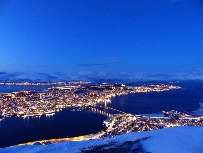 Pohled z vrcholku Storsteinen (421 m n. m.) na Tromsø: na hlavní ostrov, okolní ostrovy, hory a fjordy; duben 2016, Norsko.