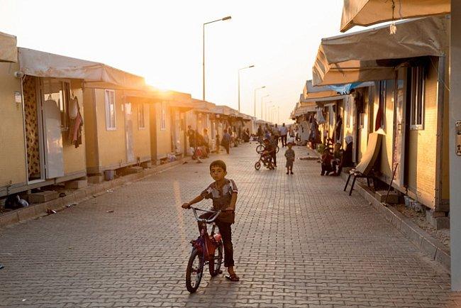 Nové improvizované domy postavené  zvelkých kontejnerů vtáboře Kilis 2 lemují  širokou ulici, po níž se pohybují hlavně děti  na kolech a dospělí pěšky.