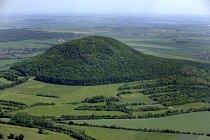 Letecký snímek hory Říp u Roudnice nad Labem. Samostatný vulkán vypadá z jihu a severu jako výrazná homole, ale z ostatních stran se ukazuje jeho výrazné prodloužení a už není ve vztahu k okolní kraji