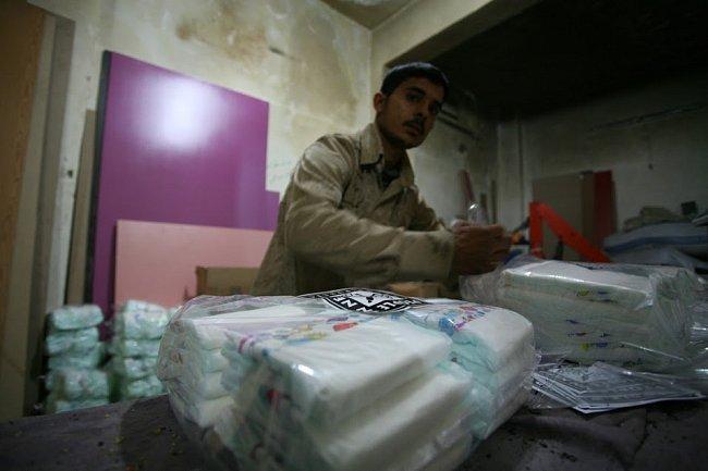 Tým Člověka v tísni spolu s dobrovolníky balí výživu pro nejmenší a plenky.