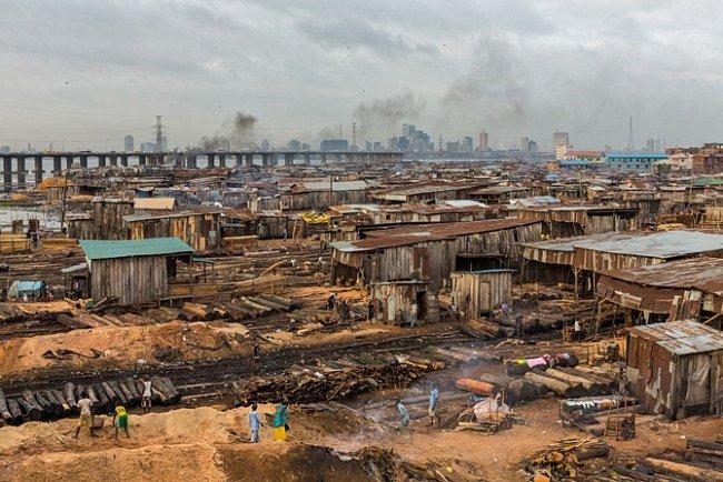 Tisíce lidí bydlí apracují večtvrti pilařských závodů vpevninském Lagosu – je to směsice dílen achatrčí, která byla zaposlední roky dvakrát zpustošena požáry. Mrakodrapy, kde se vytváří bohatství Nigérie, se vznášejí jako přízrak nadruhém břehu Lago