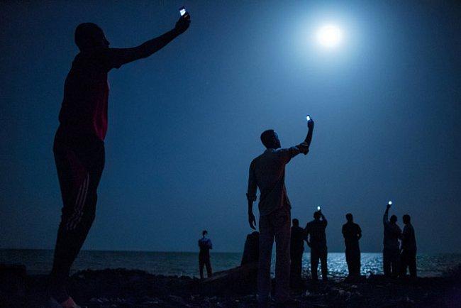 Zbídačení afričtí migranti se vnoci shromažďují napobřeží uDžíbútí asnaží se zachytit levné mobilní signály ze sousedního Somálska – nejisté spojení spříbuznými vzahraničí. Déle než 60000 let s
