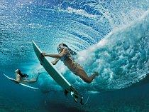 Nejlepší kamarádky Ha'a Keaulanová vpravo aMaili Makanová cestou dooceánu proplavávají pod vlnou poblíž svého domovského města Makaha. Jako generace před nimi chodí dotěchto vod téměř denně, aby občerstvily své tělo iducha.
