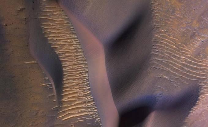 Sonda NASA Mars Reconnaisance Orbiter shlíží na svahy hory ve Valles Marineris, největším známém systému kaňonů ve sluneční soustavě. Napříč krajinou se vlní písečné duny posouvané marsovskými větry.
