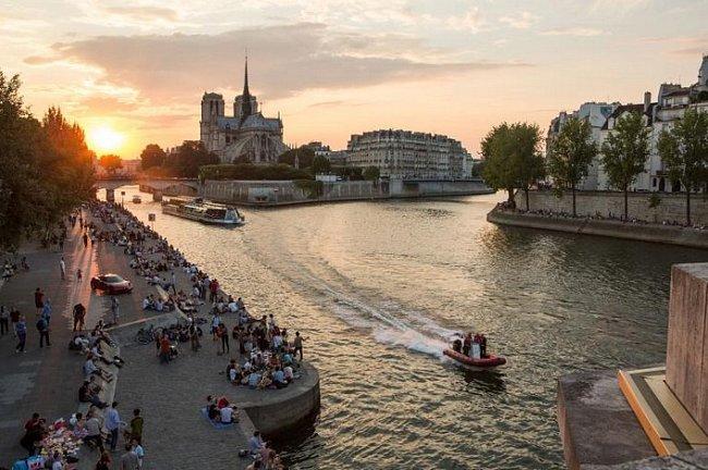 Při západu slunce se Pařížané scházejí na březích Seiny.