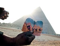 Muž ukazuje u pyramid v Gíze fotografii z lepších časů svého podnikání. Počet návštěvníků u hrobů a chrámů faraonů výrazně poklesl.