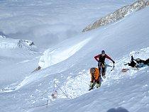 Dvojice horolezců upravuje večer plošinu pro stan.