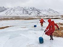 Kyrgyzské dívky vezou po ledu kanystry s vodou do rodinného tábora. Aby nabraly vodu, musely rozbít led na zamrzlém prameni. Muži mají na starosti stáda a obchod.