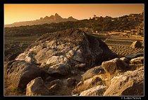 Úrodná horská krajina s městem At-Tawila v pozadí.