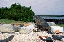 Moře vyplavuje na břeh prázdné plastové a skleněné nádoby, které znečišťují životní prostředí leguána mořského na ekvádorském ostrově Santa Cruz. Leguáni mořští žijí pouze na Galapágách.