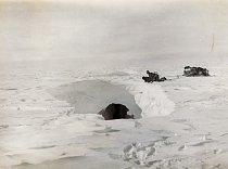 Posádka saní nahlíží do ledovcové pukliny chvíli před neštěstím. Družstvo Douglase Mawsona překonalo mnoho hlubokých puklin, než v jedné z nich zmizel Belgrave Ninnis, šest psů a důležitá výbava včetn
