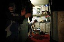Chlapec si připravuje lavor s teplou vodou, ve kterém se bude koupat. Zorin, Ukrajina