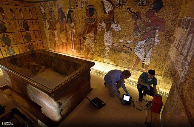 Přikrčeni u kamenného sarkofágu krále Tutanchamona připravují technici National Geographic Eric Berkenpas a Alan Turchik radar ke skenování stěny hrobky.