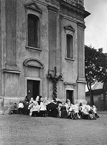 Slováci v Piešťanech při nedělní ranní mši Protože v kostele již není místo, tito zbožní lidé se mše účastní venku; klečí na zemi, přestože je vlhká a rozblácená.