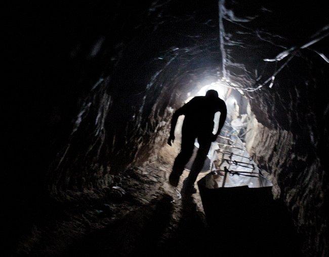 Dělník se vynořuje z jednoho ze stovek pašeráckých tunelů, jež spojují pásmo Gazy s Egyptem.