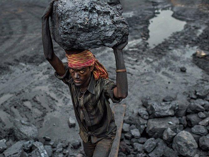 Důlní dělník Adžaj Maridžan nese kus uhlí zpovrchového dolu vBókapaharí vestátu Džhárkhand, aby jej naložil dočekajícího nákladního auta.