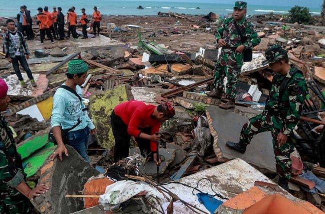 Lidé v indonéské provincii Lampung 23. prosince 2018 prohlížejí trosky po ničivém cunami. Stovky domů byly zničeny a desítky místních obyvatel zahynuly.