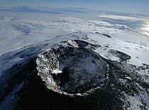 Jednoho jasného večera je hlavní kráter sopky klidný a vypouští pouze několik obláčků páry. Sousedí s ním další, nyní už neaktivní kráter. Za ním se rozprostírá snová krajina tvořená mořským ledem a o