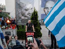 Příslušník Zlatého úsvitu uctívá památku Manolise Kapelonise aGiorgose Fountoulise, kteří byli zastřeleni vlistopadu 2013 odplatou zasmrt antifašistického rappera Pavlose Fyssase.
