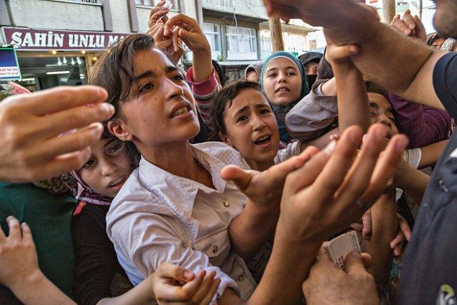 Přibližně 350000 Syřanů, kteří se usadili ve městě Gaziantep a okolí, nemá snadný život. Ženy a děti se shlukují kolem pracovníka pekařství vydávajícího kupony na bezplatný chléb.