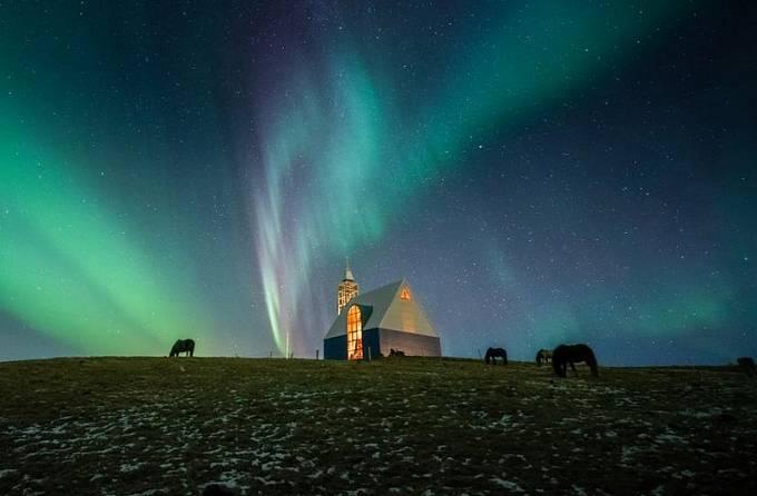 """Polární záře tančí na noční obloze nad kostelem a koňmi v Selfossu na Islandu. """"Poté, co jsem několik hodin fotografoval, jsem fotoaparát odložil a šel se dovnitř ohřát. V tu chvíli se obloha znovu rozzářila barvami,"""" říká autor snímku Jaynie Bunnell."""