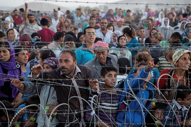 Etničtí Kurdové, jejichž domovy vSýrii, ve městěAjn al-Arab (Kobane), jsou vystaveny útokům, zatlačují plot zostnatého drátu na tureckých hranicích.