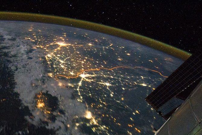Zřetelná oranžová řada světel, která se hadovitě vine středem fotografie je oplocená a bohatě osvětlená hraniční oblast mezi Indií a Pákistánem.
