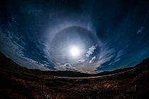 Obrovský kruh okolo měsíce na fotografii není optický kaz, nýbrž fyzikální jev zvaný halo. Vzniká průchodem světelných paprsků skrz ledové krystalky v atmosféře. Zhruba jednou za rok jej lze pozorovat