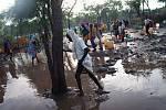 Ženy a děti se brodí vodou a bahnem, aby si naplnily své kanystry u distribučního místa pitné vody v táboře Batil. Silné deště a záplavy v táboře zhoršili už tak špatný stav vodních zdrojů a sanitace.
