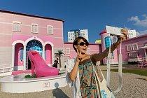 """Odlišný obrázek zcentra Berlína: """"Barbie: domov snů"""" – plátěný domek pro panenky vživotní velikosti svodotryskem vpodobě růžového střevíce navysokém podpatku."""