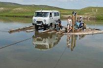 Členové archeologické expedice pomáhají táhnout dřevěný prám přes řeku v mongolském údolí Darhad.