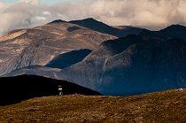 Jirka Černý (autor textu článku) s baťohem na cestě Grónskem, v pozadí pohoří Isunngua.