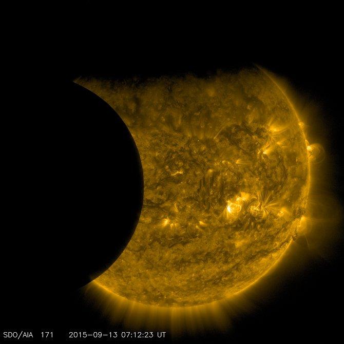 Slunce částečně zastíněné Zemí (zhora) a Měsícem (zleva). Jeho okraj je dokonale ostrý, protože nemá žádnou atmosféru, která u Země blokuje různé množství světla v různých výškách.
