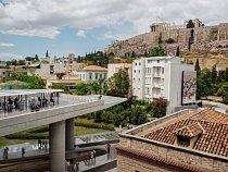 Moderní symbol národní hrdosti, muzeum Acropolis (vlevo), částečně financované zprostředků Evropské unie adokončené roku 2007, vzhlíží kvěhlasné řecké pamětihodnosti − Parthenonu.