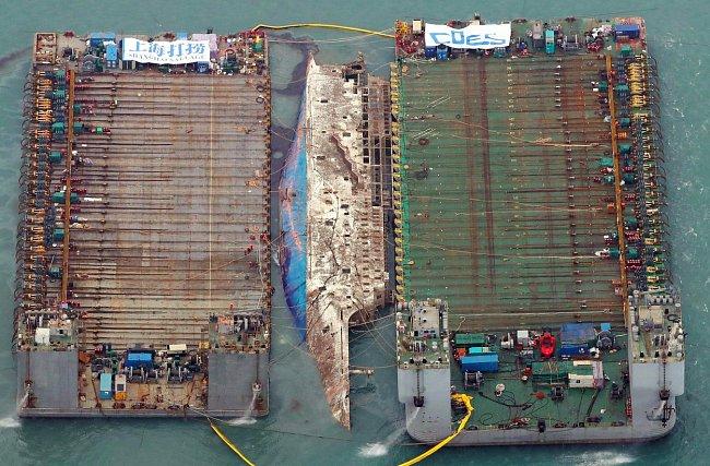 Část poškozeného trajektu mezi dvěma čluny poté, co byl vyzvednut nad hladinu.