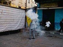 Zatímco demonstranti a bezpečnostní síly bojují o osud Egypta, život pokračuje v obvyklém rytmu. Muž v oblaku kouře po malé rachejtli vypálené na oslavu svatby v Alexandrii.
