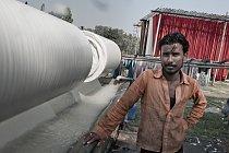 Vedle nádrží se pomalu otáčí velké válce, na kterých jsou navinuté světlé pásy tkanin. Procházejí betonovým žlabem s vybělovací lázní.