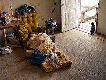 Mladý muž postižený neurologickou chorobou a alkoholismem spí v obývacím pokoji svého domu, který stojí asi deset kilometrů od nejbližšího města. Snímek byl pořízen v květnu 2011; později byl dům urče