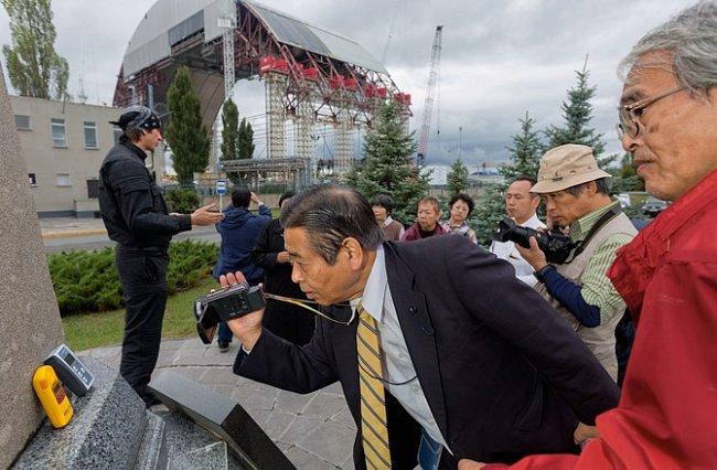 Turisté, z nichž někteří žili poblíž fukušimské jaderné elektrárny, opírají Gaigerovy-Müllerovy počítače o památník, aby zjistili, jak blokuje záření  z reaktoru, který bude zakrytý novou klenbou o hmotnosti 32000 tun.